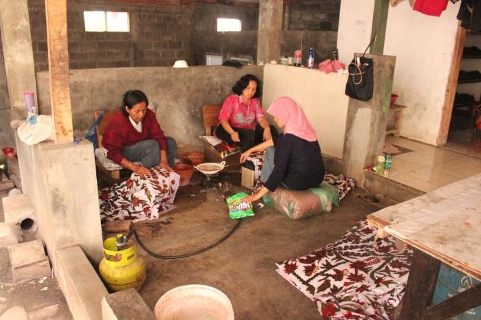 Ibu-ibu tengah membersihkan  potongan-potongan kain hasil pewarnaan yang melenceng dari motif.