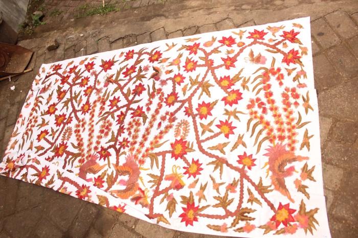 Sepotong kain tengah dijemur diatas tanah seusai pemberian warna dasar dan pencucian.