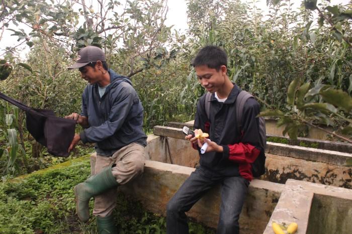 Wandi (kiri) saat berbincang dengan anggota Lirik Malang, Rizqy di kebun yang ia garap