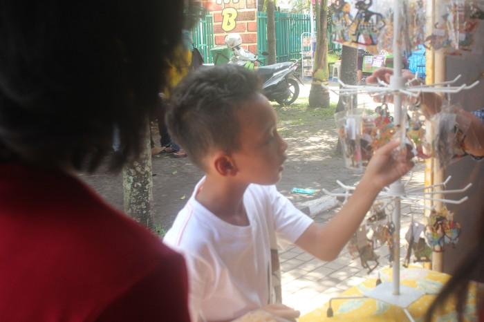 Seorang anak pengunjung MBF tengah melihat-lihat gantungan kunci bermotif tokoh-tokoh wayang di Stand Wayang.
