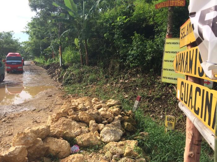Akses jalan masuk menuju Pantai Goa Cina yang masih tanah dan bebatuan besar.